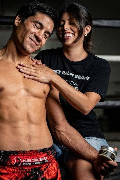Woman rubbing intensive relief cream on Asa Ten Pow professional Muay Thai fighter and champion