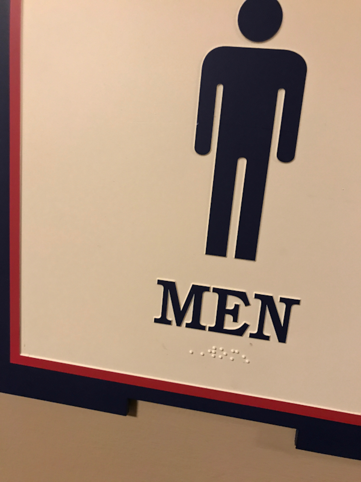 Men's restroom sign with Women in braille