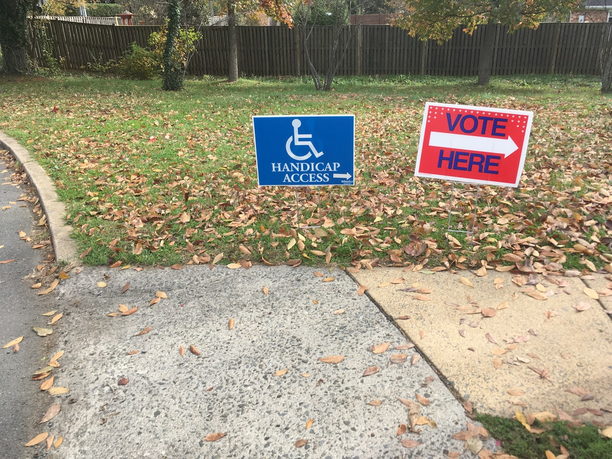 Two signs next to a curb ramp. Vote Here. Handicap Access