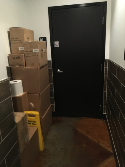 A hallway where all the space for wheelchair navigation into the restroom has been filled with boxes.