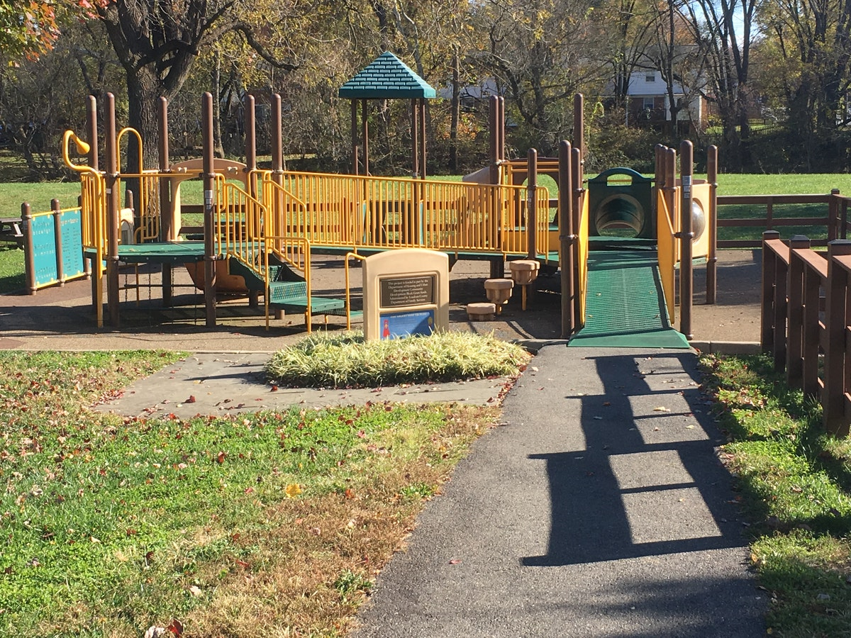 A two level playground with a path leading to a ramp that leads up to the second level. Additional activities around the playground are wheelchair friendly.