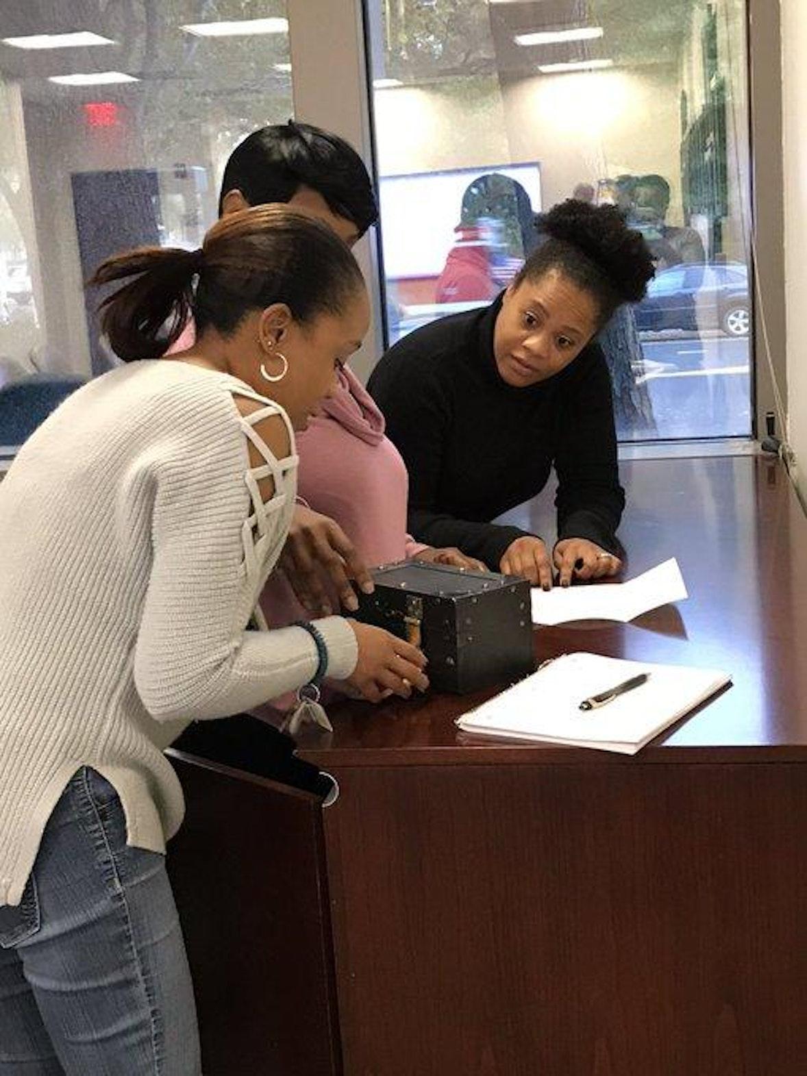 Three women work on opening a box
