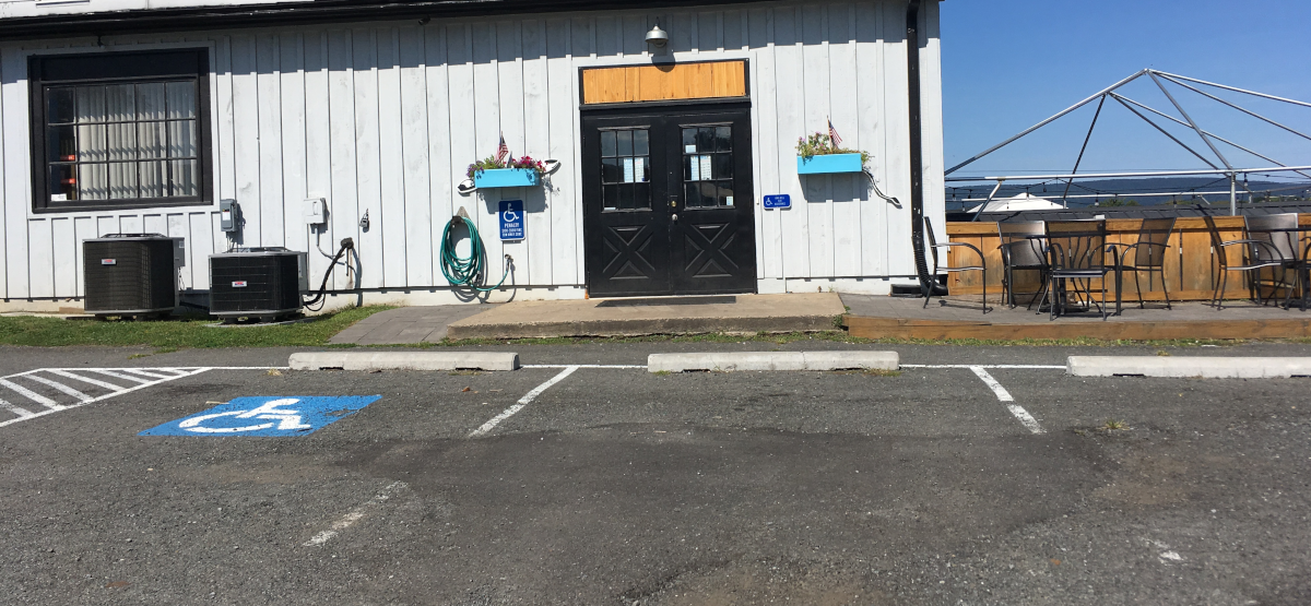 A restaurant with accessible parking leadign to a wheelchair accessible eating area. A call button is available if someone in a wheelchair nees service.